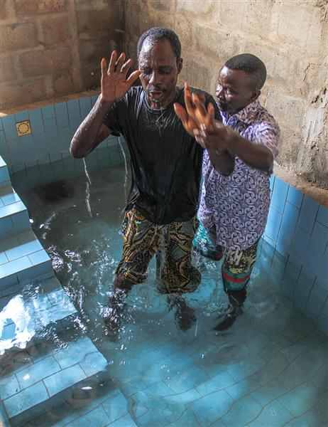 Ekpli Lord Lugard is baptized by Esperance Mensah in the meeting place of the Nukafu Church of Christ in Lomé