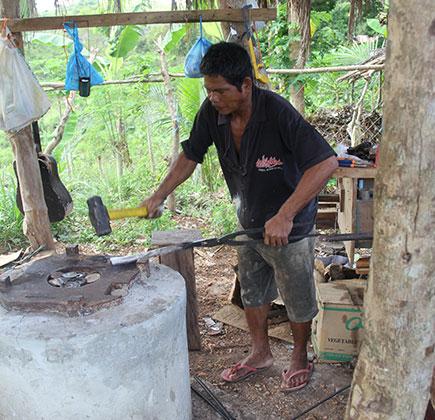 A blacksmith hammers plow sweeps into machetes. (Photo by Erik Tryggestad)