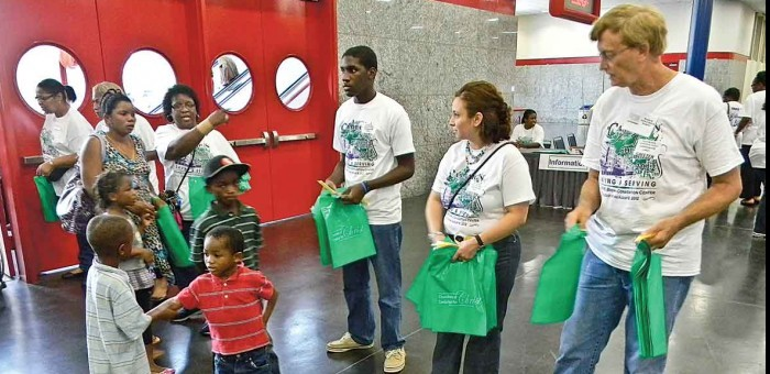 Two boys shake hands as Campaign for Christ volunteers welcome needy residents to a Houston convention center in 2012.