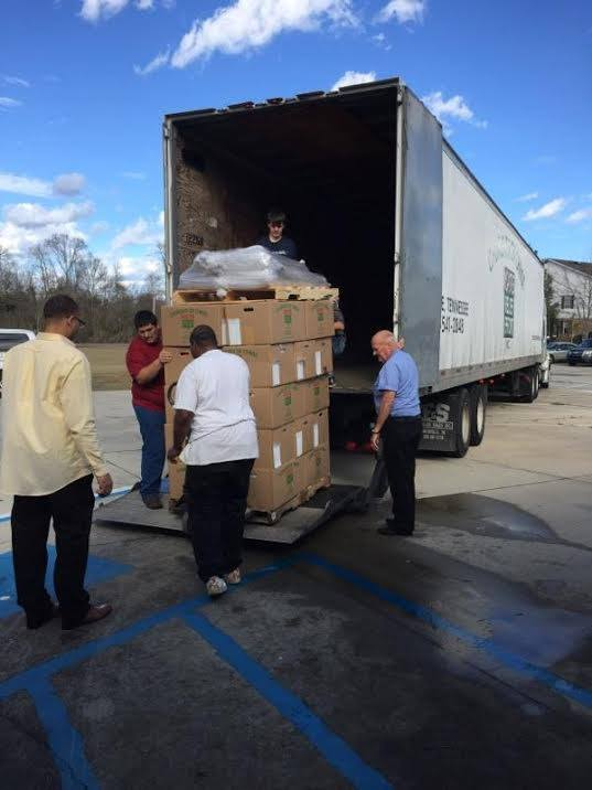 Volunteers unload a truck full of supplies at the Kensington Woods church building in Hattiesburg
