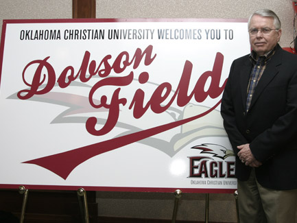 Max Dobson stands with a sign bearing his name after an alumni dinner. A surprise announcement — that the Oklahoma Christian baseball field would be named after Dobson and his late wife