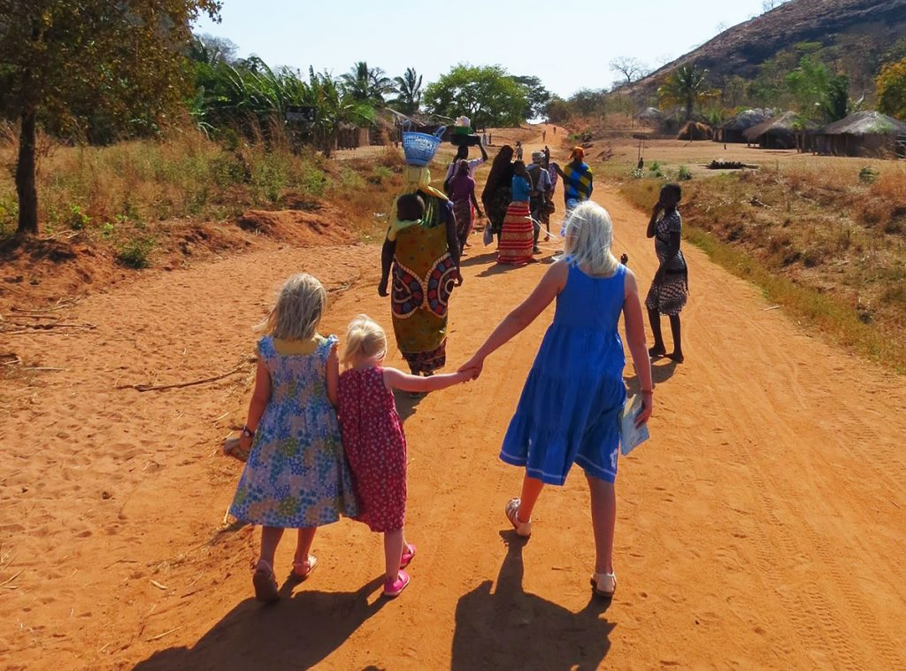 The three daughters of Alan and Rachel Howell walk behind a group of women in Mozambique.