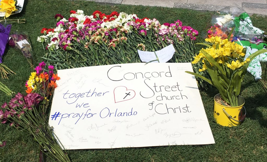 The flowers and poster left at the memorial site by members of Churches of Christ.