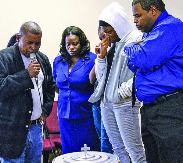 John Ellis prays as Angela Marsalis, Shekeira Honor (hidden behind Angela), Kevinisha Honor and Charles Marsalis bow their heads.