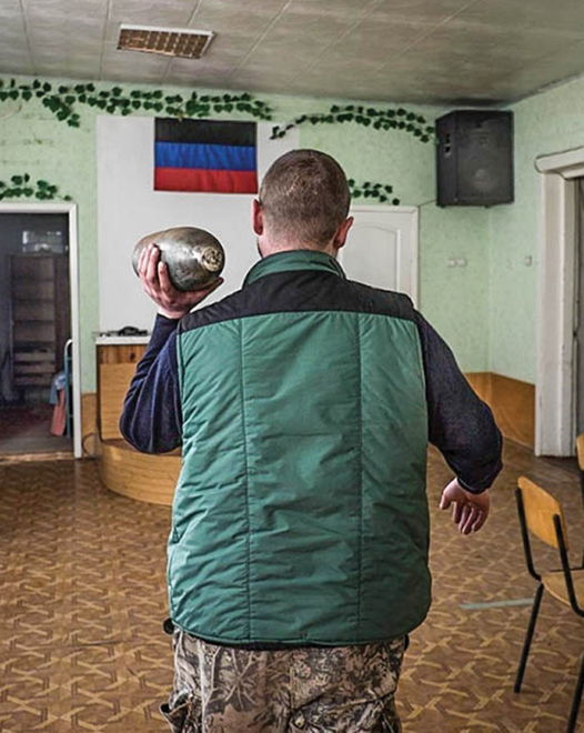 A separatist fighter carries a live artillery shell through the former meeting place of the Petrovsky Church of Christ in Donetsk