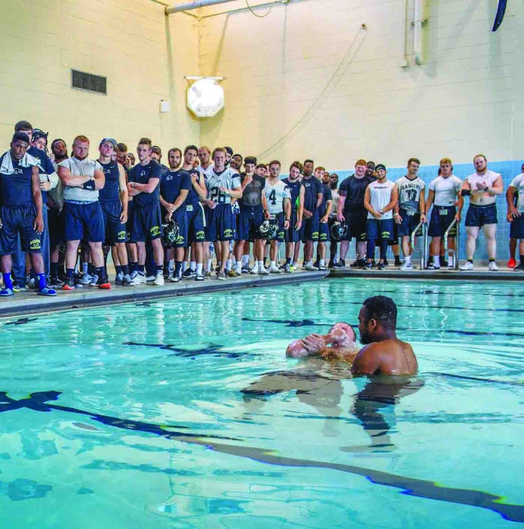 In a swimming pool on the campus of Harding University in Searcy, Ark., football player Jordan Allison baptizes his fellow offensive lineman Braden Hood as their teammates watch. Across the nation, student athletes at universities with church ties made headlines recently for misconduct and crime. Coaches, trainers and athletic personnel at colleges and universities associated with Churches of Christ talked to The Christian Chronicle about their efforts to keep players out of trouble — and in the Word. Some schools have created positions focused specifically on players' spiritual needs.