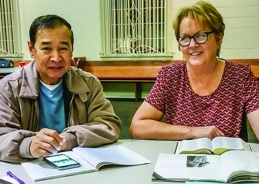 Bora Durn from Cambodia reads with Long Beach Church of Christ member Denise Rash.