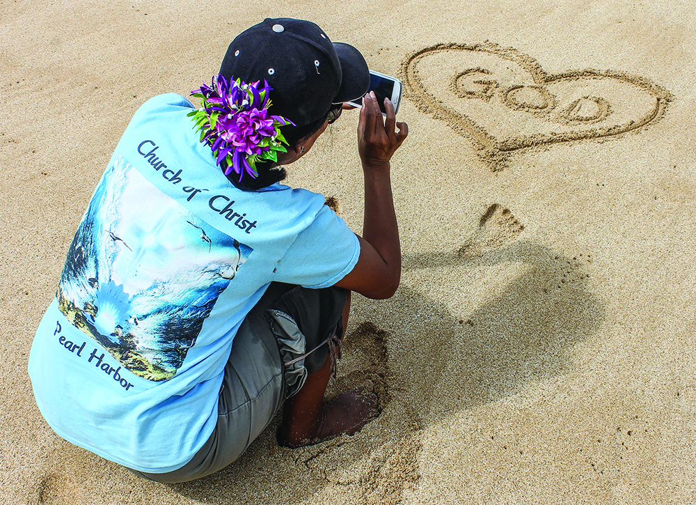 "Minister's wife Ruth Byrne snaps a photo of a ""Love God"" symbol she drew in the sand on the Hawaiian island of Oahu's North Shore."