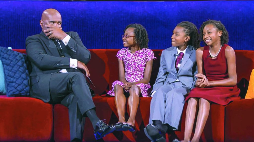 "The Johnson kids sit on stage with Steve Harvey during filming of ""Little Big Shots."""