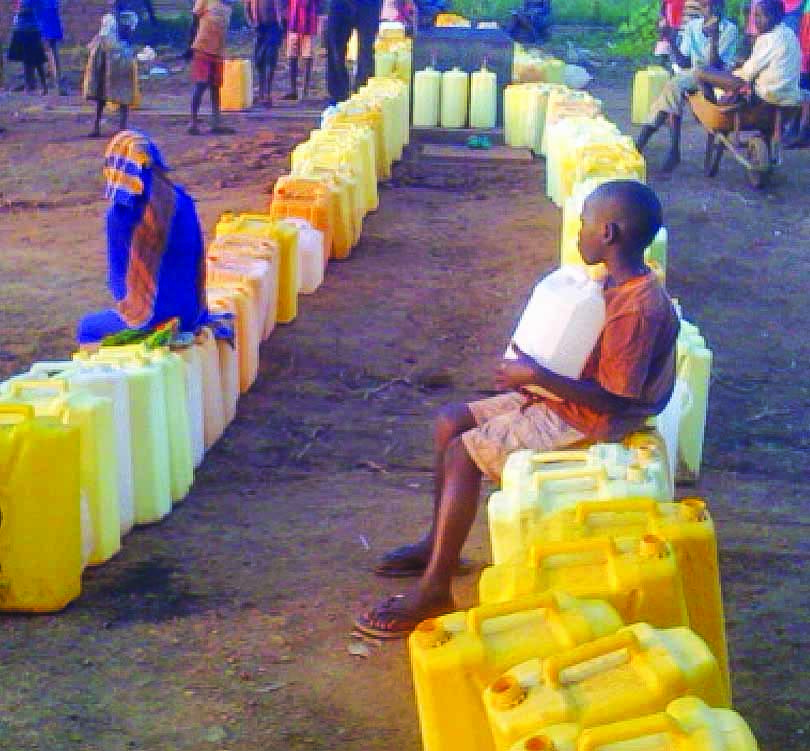 A child waits for water at a refugee camp in Uganda.
