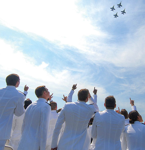 Midshipmen watch a flyover from the Pukin' Dogs of Strike Fighter Squadron 143 during a graduation and commissioning ceremony at the U.S. Naval Academy in Annapolis