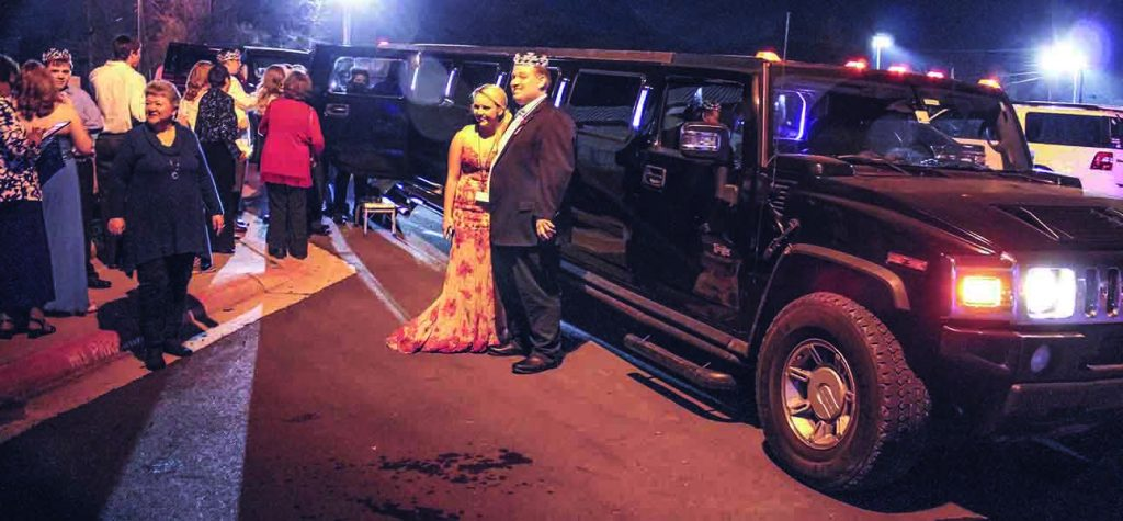 """King"" Austin Peters basks in the spotlight of Night to Shine as he and his volunteer buddy prepare to board a limousine."