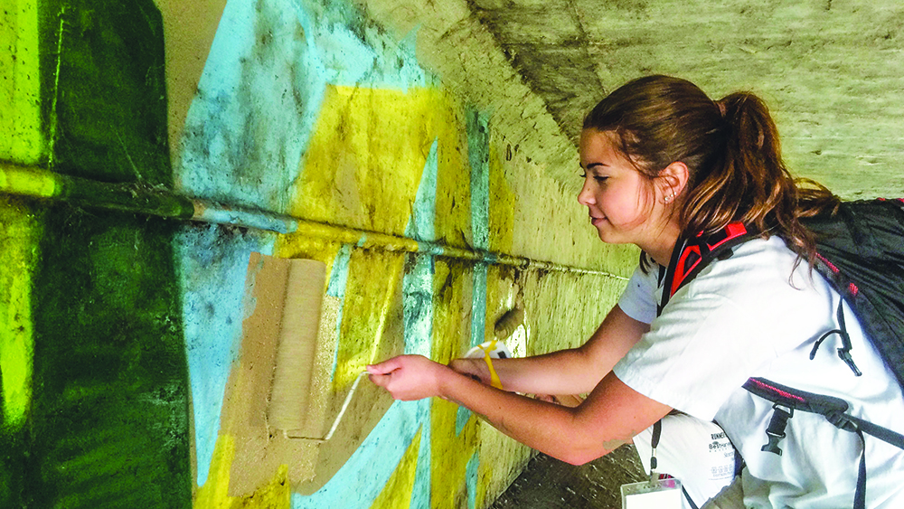 Abby deSteiguer from the Memorial Road Church of Christ in Oklahoma City works on a painting project during the Wichita Work Camp.