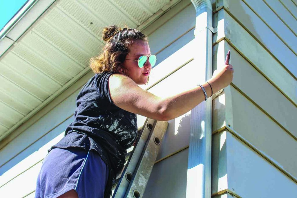 A participant in the Mid-Ohio Valley Work Camp paints Elizabeth Carro's home.