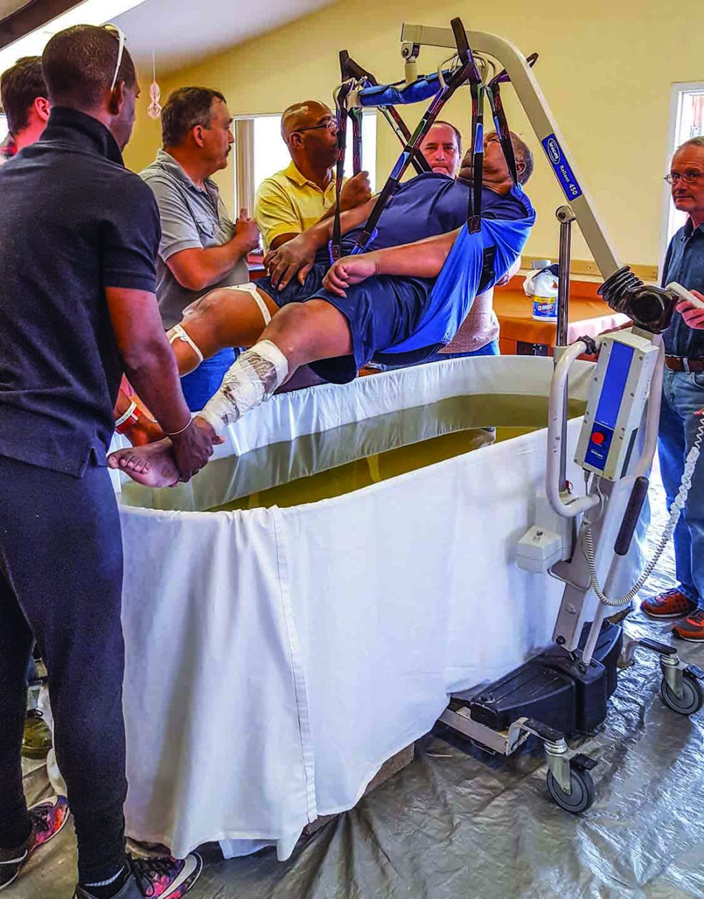 Men from the Gallup Church of Christ in New Mexico use special equipment to lower Tommy Fields into a baptistery.