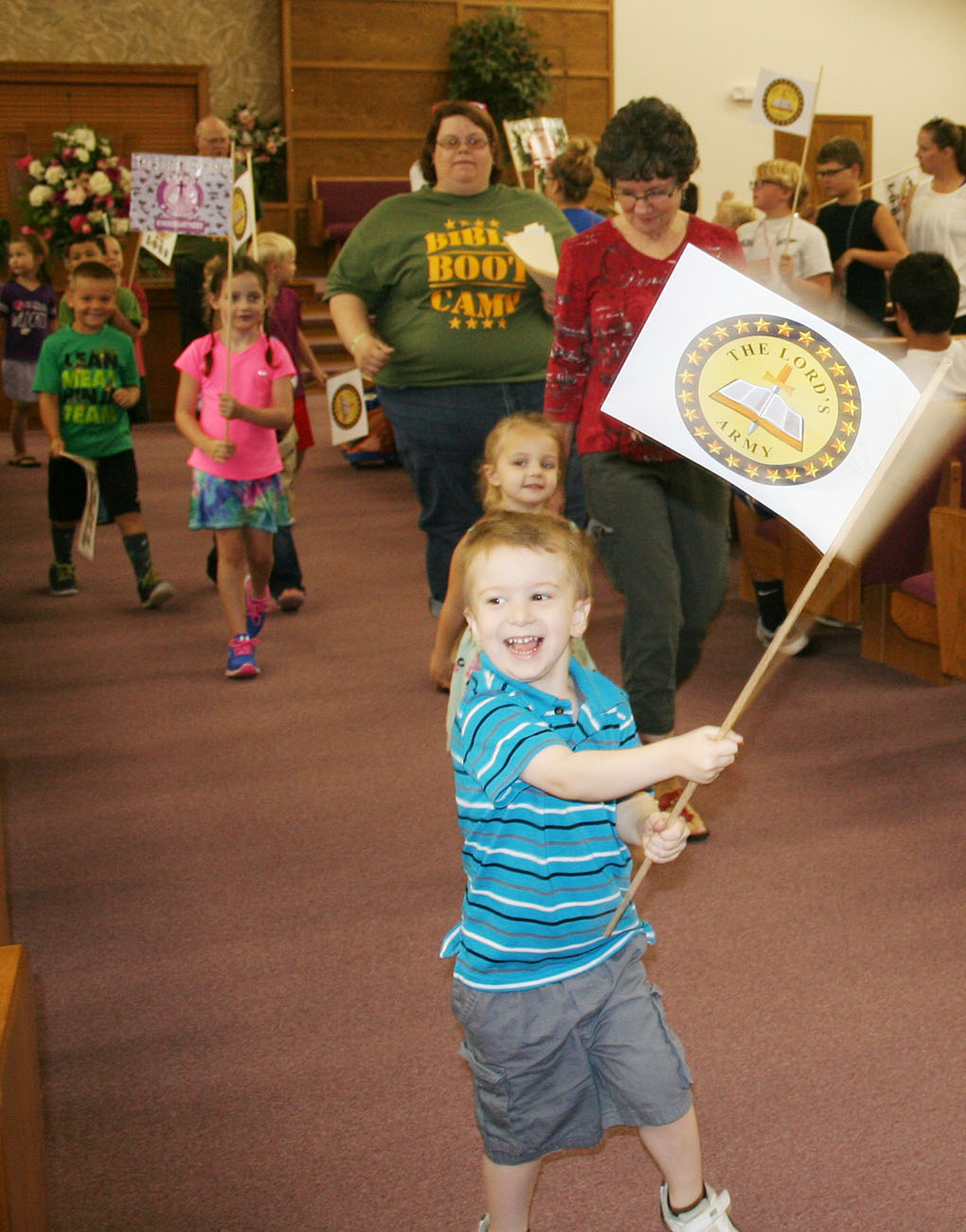 A child carries a flag as part of a Vacation Bible School at the Augusta Church of Christ in Kansas.
