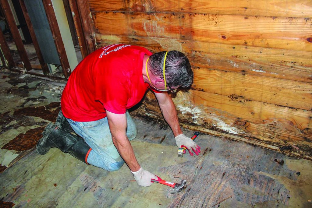 Church member Randy McMaster works to remove rotted wood from a Baton Rouge home.
