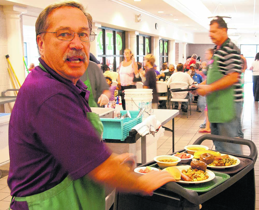 "A volunteer serves hot meals at the no-questions-asked ""Lord's Diner"