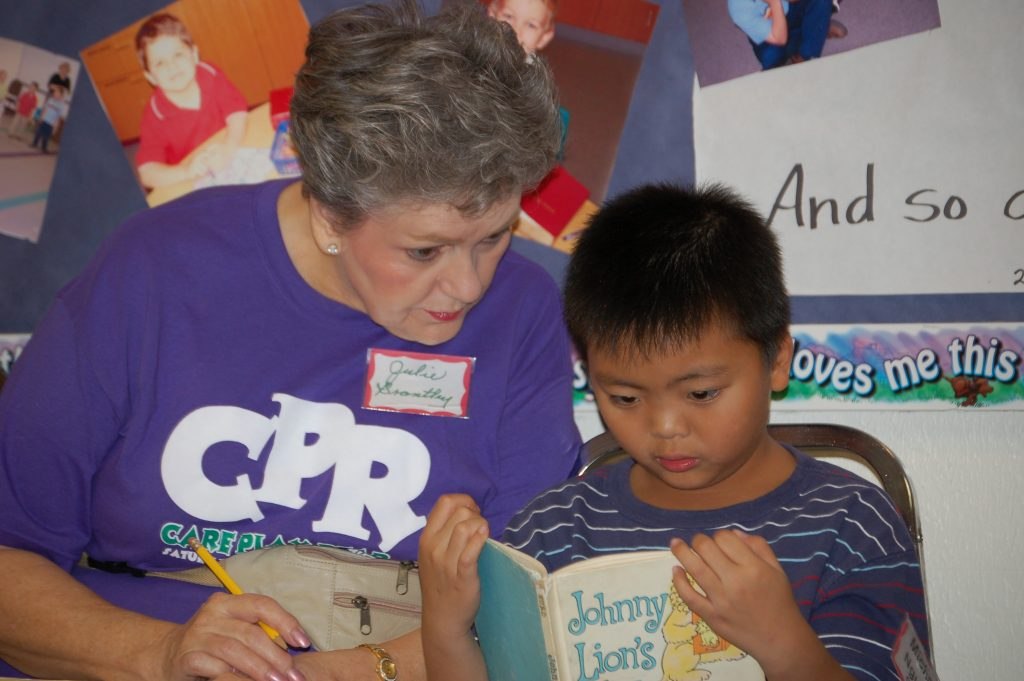 Julie Brantley reads with Michael Nguyen as part of the Care Play Read summer program at the Saturn Road church in Garland