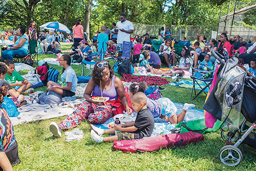 "Members of the Harlem Church of Christ in New York dine and enjoy the sunshine during a barbecue ""Love Feast"" at the Van Cortlandt Park track in Bronx"