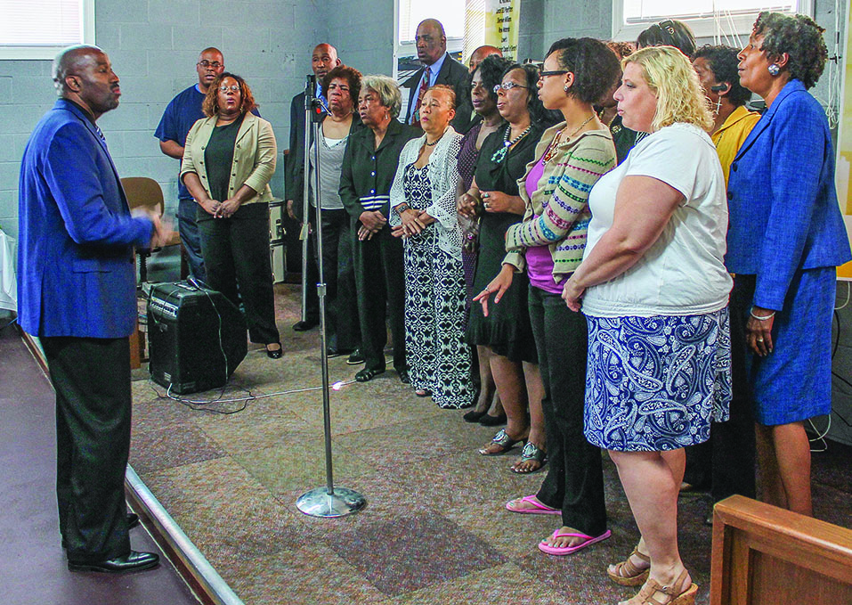 A group of Roswell Church of Christ members sings during the dedication ceremony for the Village Initiative Inc. resource center.