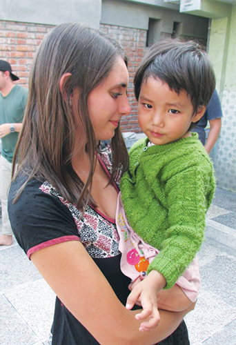 Savannah Holladay with a child she serves in Nepal.
