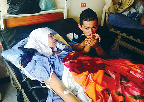 One of Wilfredo and Reina Rios' two sons sits by his mother's bedside at a hospital in Tegucigalpa