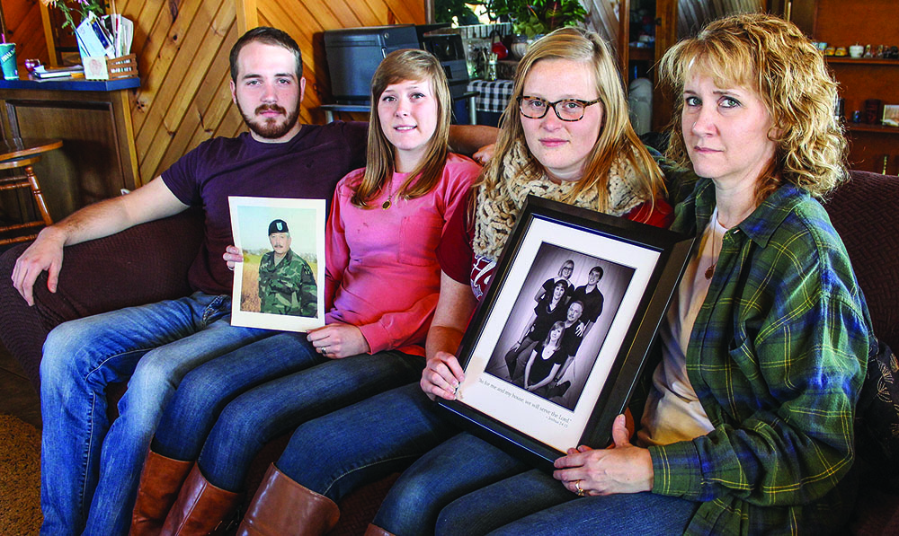 Family members of Timothy Harris hold photos remembering their loved one. Pictured