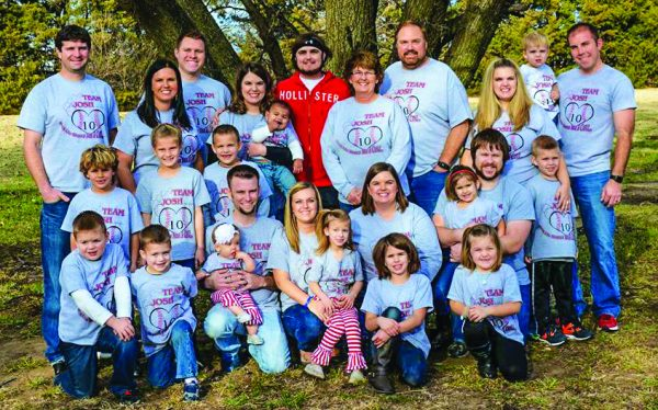 eart transplant recipient Josh Oakley, top center in red, poses with his extended family — including his parents, sisters, brothers-in-law, nieces and nephews.