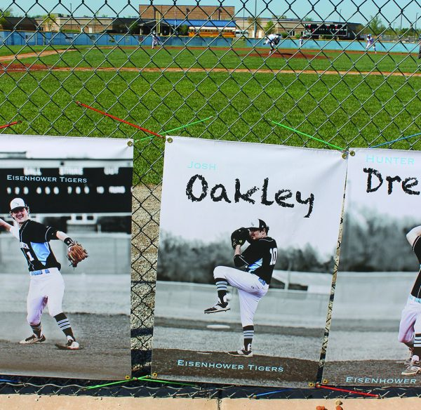 A picture of Josh Oakley hangs on the fence at the Eisenhower High baseball field in Goddard, Kan.
