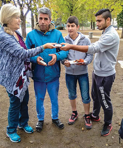 "Reggy Hiller gives Arabic New Testaments to refugees from the Middle East. ""We now have 10 new refugees from three different countries attending worship services regularly as a result of this outreach"