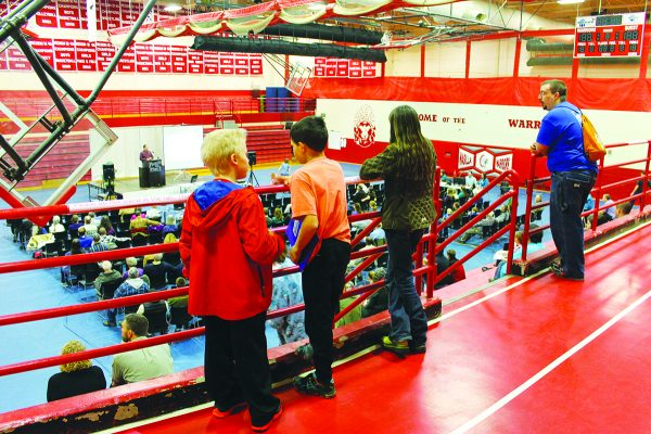 Children watch from the bleachers during a session of the Alaska Statewide Lectureship at the Wasilla High School gymnasium.