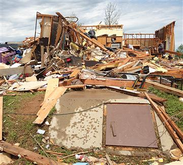 The remains of the Legers' home after the tornado. The storm shelter in the foreground likely saved their lives.
