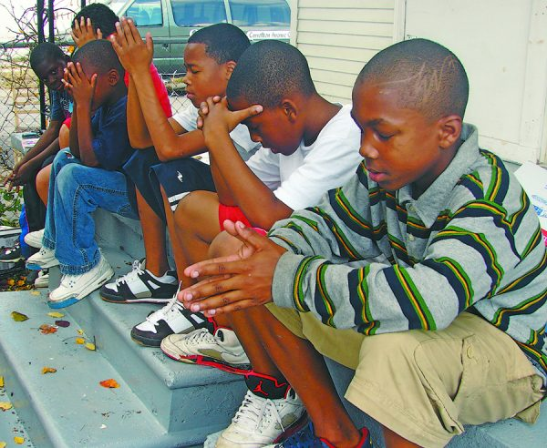 In 2008, Ishmel Wiltz, right, and other boys pray during a Saturday morning Bible study on a flood-damaged home's porch in New Orleans.