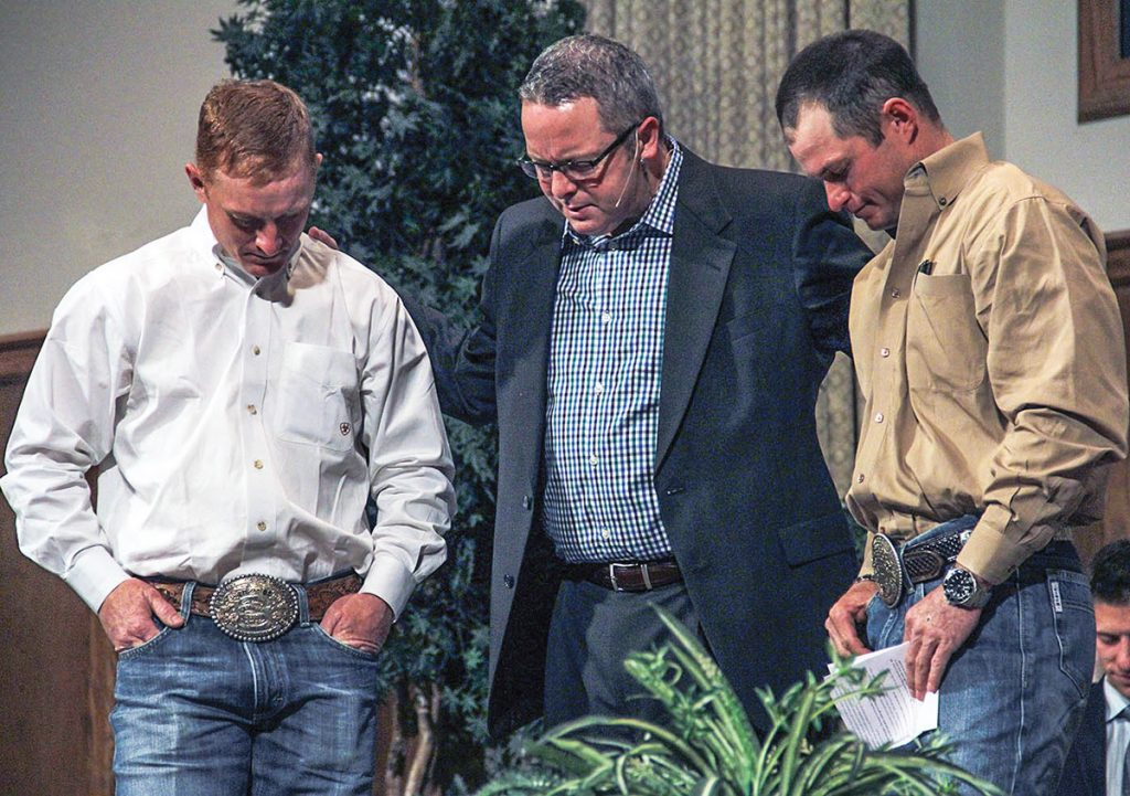 Scott Young prays with Cord and Jet McCoy at the Memorial Road Church of Christ in Oklahoma City. The McCoys