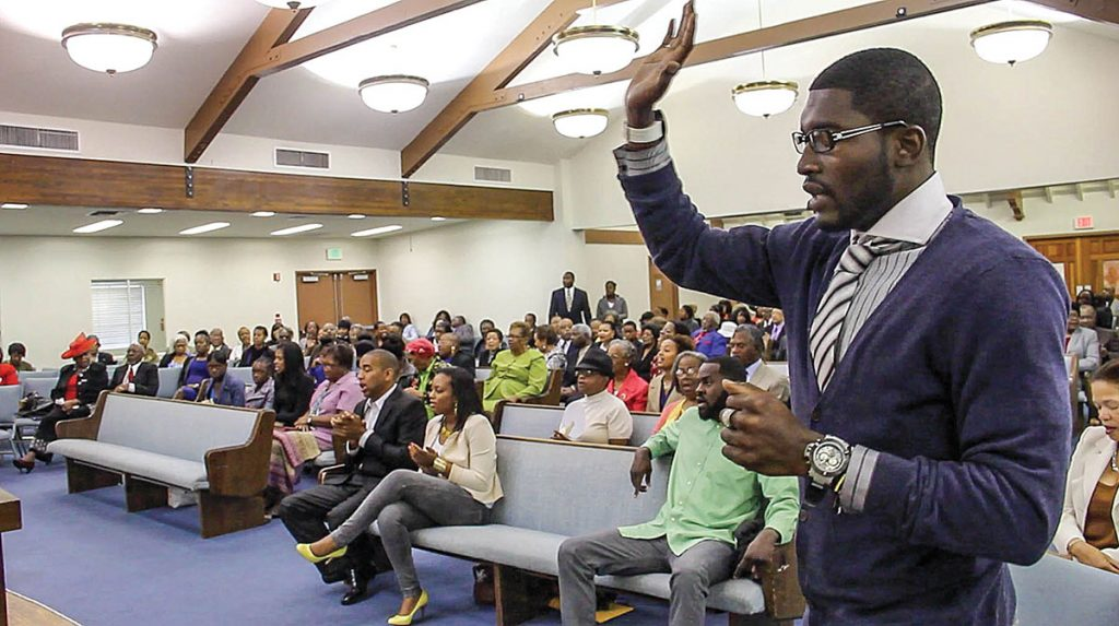 "Troy Andrews raises his hands as he and fellow members of the Crenshaw Church of Christ in Los Angeles sing ""I Love to Praise His Holy Name."" The church has two Sunday morning services."