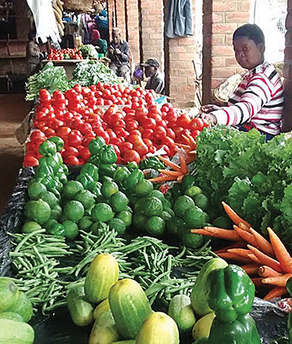 Piles of vegetables and fruits line the tables of an open-air market Zomba