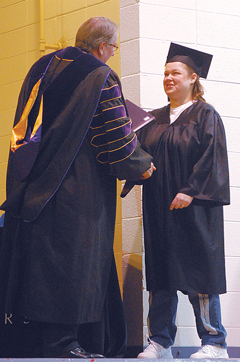 Erika East receives her diploma and congratulatory handshake from Lipscomb University president L. Randolph Lowry during a graduation ceremony at the
