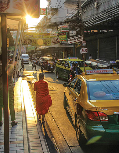 A Buddhist monk walks along the crowded streets of Bangkok