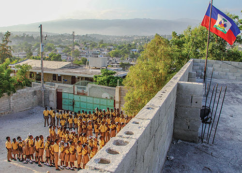 At Cazeau Christian Elementary School, on a hilltop overlooking Port-au-Prince, Haitian children pledge allegiance during a Friday morning flag-raising ceremony in 2015. The school is supported by Hope for Haiti's Children.