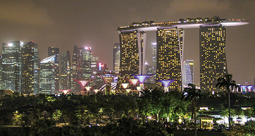 "The luxurious Marina Bay Sands Hotel towers over a grove of ""supertrees"" — solar-powered"