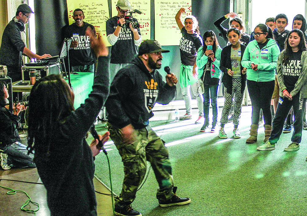 Jason Darden performs for children during a Triple Threat Mentoring event at a California elementary school.
