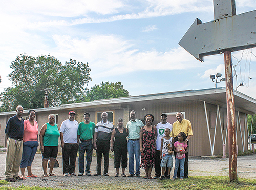 Roswell Church of Christ members and leaders gather outside a one-time dry cleaners being transformed into a resource center.