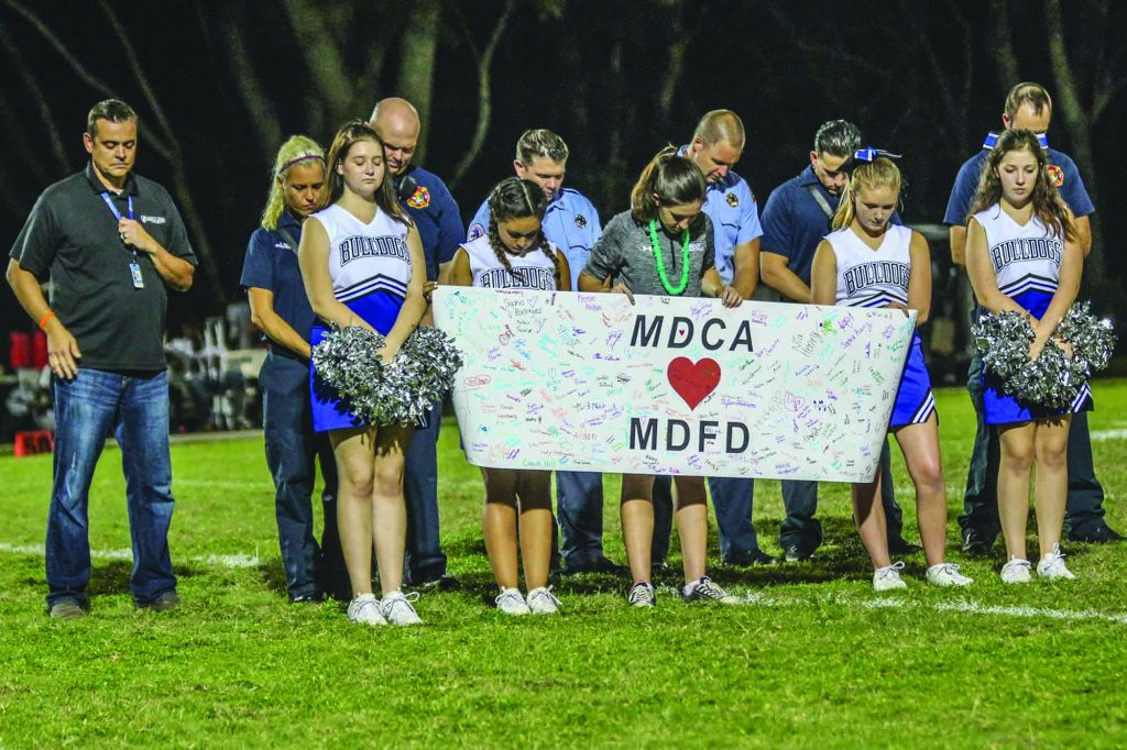 Cheerleaders and first responders bow in prayer at a Mount Dora Christian Academy football game in Florida. The K-12 school