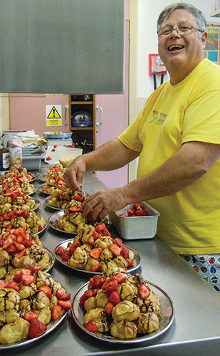 Trevor Williams prepares profiteroles (cream-filled pastries) with strawberries and chocolate sauce during a Christian camp in Leicestershire