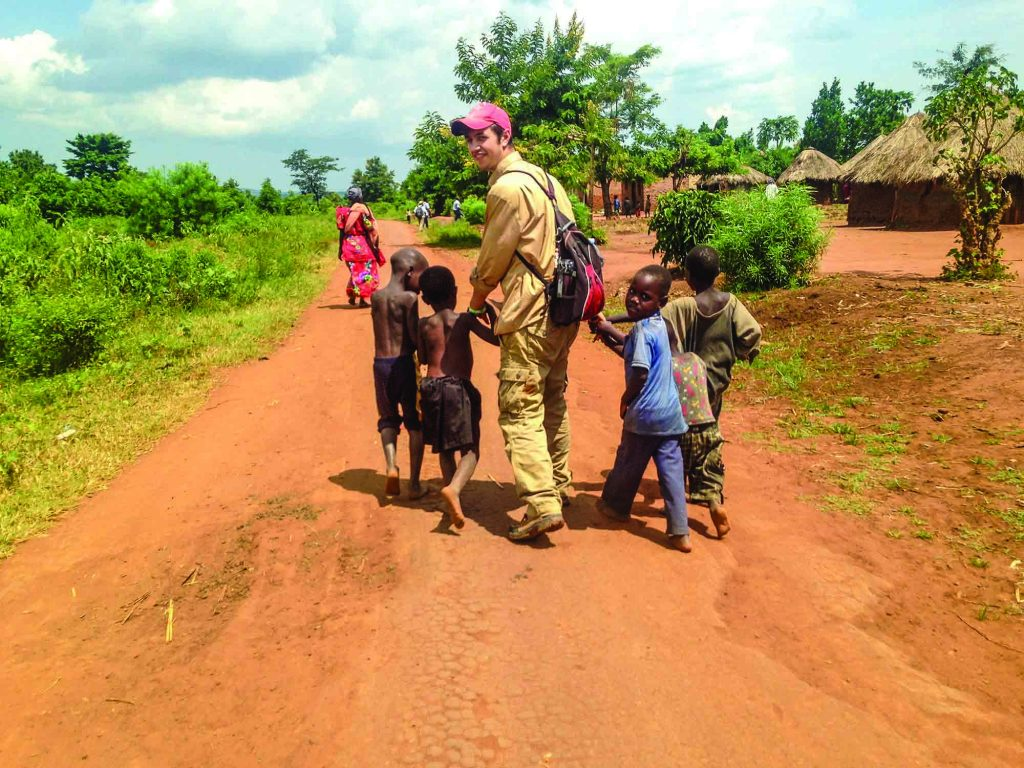 Rochester student Rory McAllister visits children in a Ugandan village.