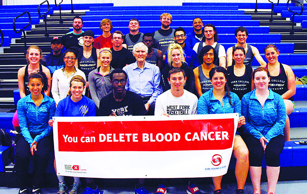 Track and field athletes at York College in Nebraska surround Earl Young