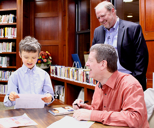 A boy shows Lee Strobel a picture he drew as minister David Young watches.