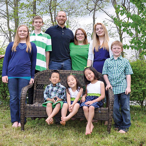 Kenny and Wendi Rogers — and their seven children — in a family photo.