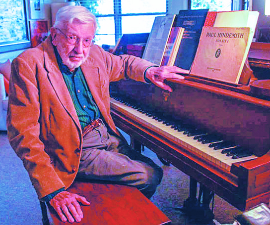 Harold Fletcher sits at his home piano. He retired on his 91st birthday